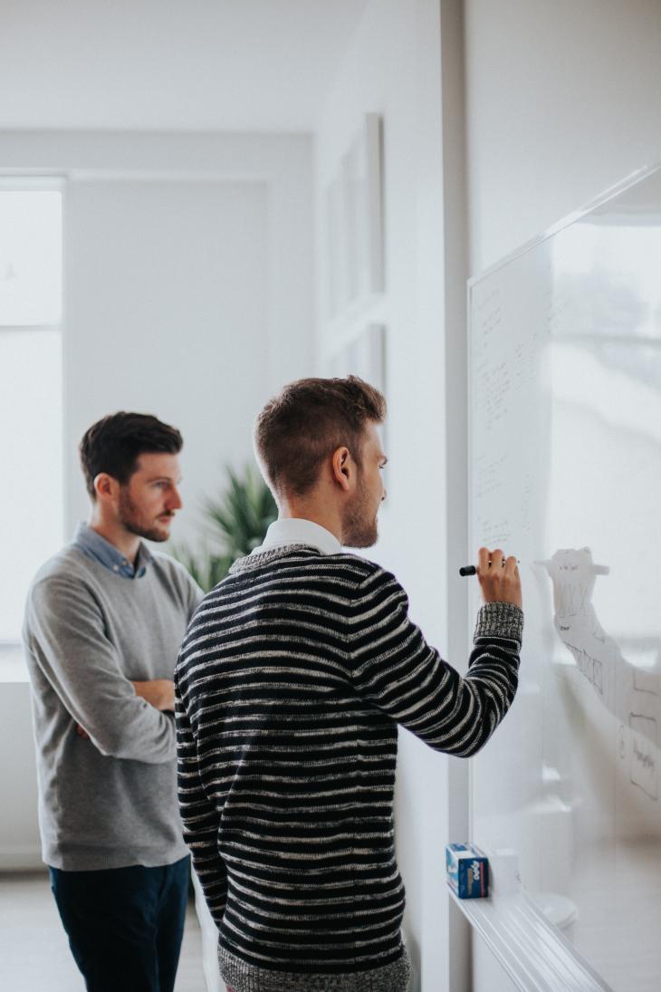 2 hommes écrivent sur un tableau blanc